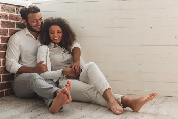 Amerikaans echtpaar in slimme vrijetijdskleding knuffelt.