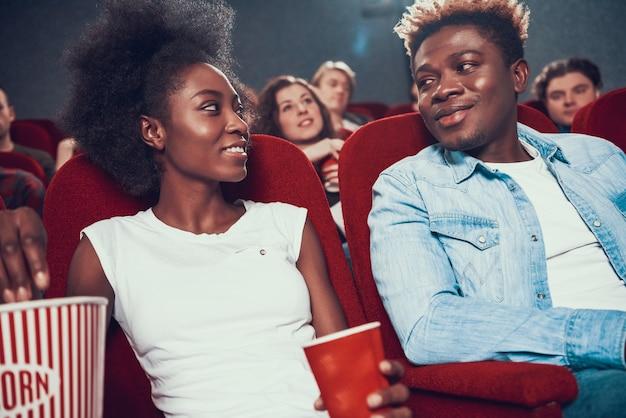 Amerikaans echtpaar met popcorn kijken naar film in de bioscoop.