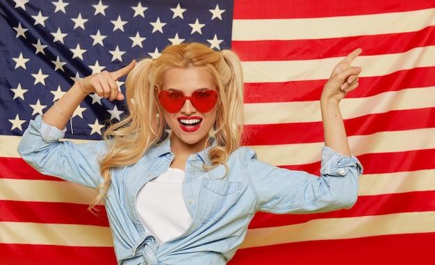 Amerikaans meisje. gelukkige jonge vrouw in de zonnebril van de hartvorm op de vlagachtergrond van de vs grappig en verrast menselijk gezicht. patriottisme concept