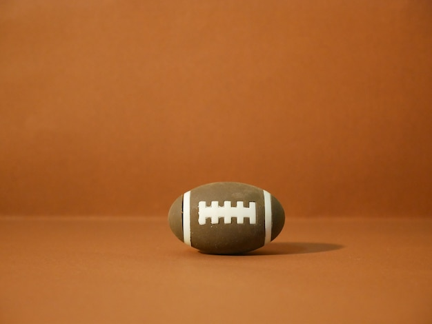 Amerikaans voetbal met exemplaarruimte op bruine achtergrond