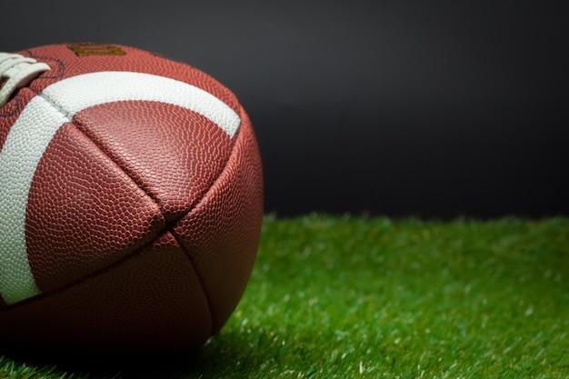 Amerikaans voetbal op groen gras op zwarte achtergrond