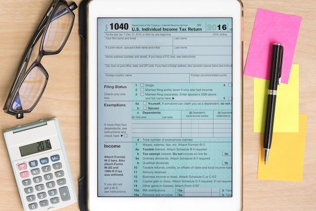 Amerikaanse belastingformulier 1040 in tablet met rekenmachine en pen