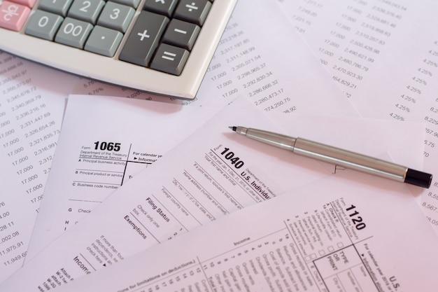 Amerikaanse belastingsvorm met pen en calculator selectief nadruk / belastingsconcept