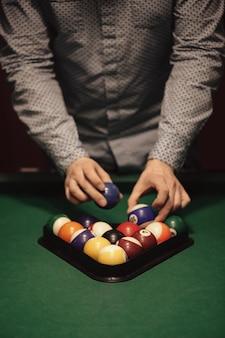 Amerikaanse biljart poule. driehoek van biljartballen. een man die zich klaarmaakt om een spelletje biljart te beginnen.