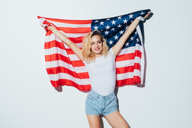 Amerikaanse blonde vrouw die de vlag van de vs houdt die over een witte muur wordt geïsoleerd