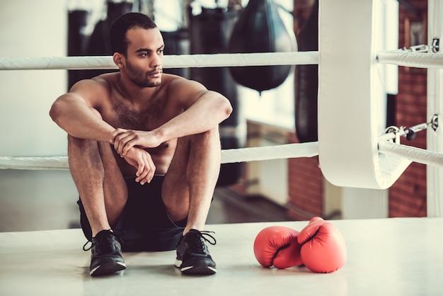 Amerikaanse bokser met blote torso kijkt weg.