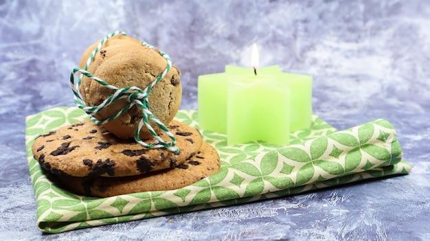 Amerikaanse chocoladeschilferkoekjes in een stapel gebonden met draad op een groen servet en een kaars. traditioneel afgerond knapperig deeg met chocoladeschilfers. bakkerij. heerlijk dessert, gebak.