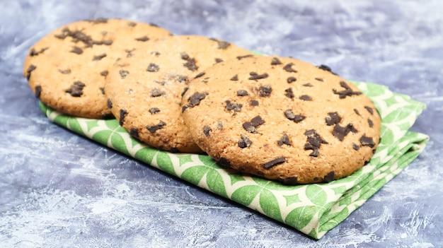 Amerikaanse chocoladeschilferkoekjes op een groen servet op een grijze achtergrond. traditioneel rond krokant deeg met chocoladeschilfers. bakkerij. heerlijk dessert, gebak.
