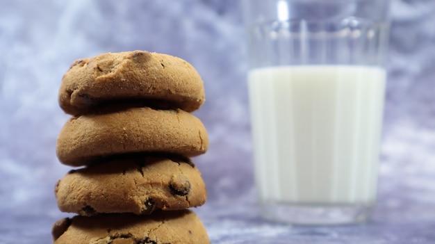 Amerikaanse chocoladeschilferkoekjes op elkaar gestapeld met melk in een glas op een grijze achtergrond. traditioneel afgerond knapperig deeg met chocoladeschilfers. bakkerij. heerlijk dessert, gebak.