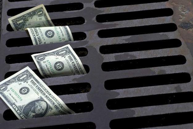 Amerikaanse dollarbiljetten in de straatafvoer