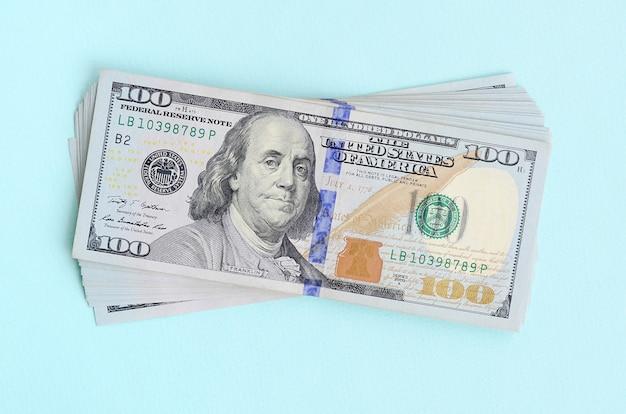 Amerikaanse dollarbiljetten van een nieuw ontwerp met een blauwe streep in het midden zijn leugens op een lichtblauwe achtergrond