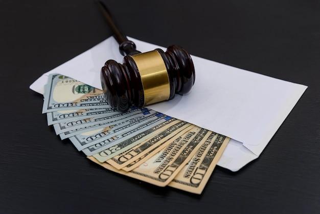 Amerikaanse dollars in envelop met de hamer van de rechter op donker