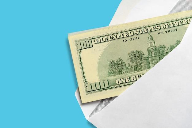 Amerikaanse dollars in open witte postenvelop op blauw