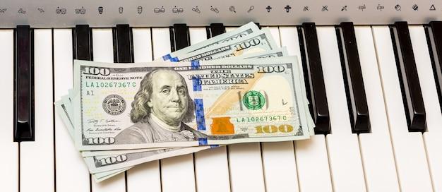 Amerikaanse dollars liggen op de pianotoetsen. betaling voor het concert, profiteren van het uitvoeren van muziekwerken