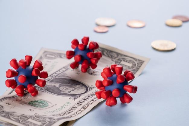 Amerikaanse dollars, munten en modellen van covid-19-virus besmet besmet contant geld. economiecrisis