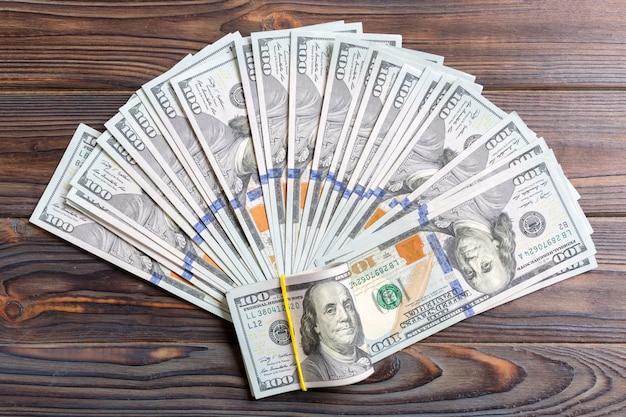 Amerikaanse dollars: onordelijke fan verschillende amerikaanse dollarbiljetten bovenaanzicht bedrijf op gekleurd