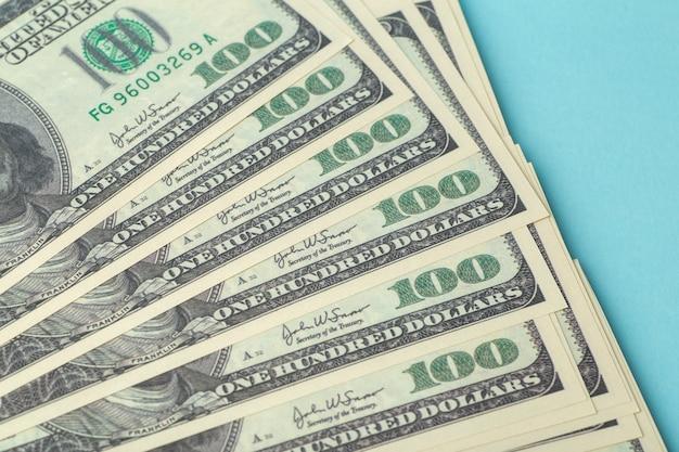 Amerikaanse dollars op tafel. honderd (100) dollar neergelegd op een blauwe achtergrond. amerikaanse valuta en economie, wisselkoersen, internationale economie en marktconcept