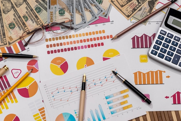 Amerikaanse dollars op zakelijke grafieken met pen en rekenmachine