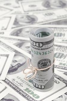 Amerikaanse dollars opgerold en aangespannen met band ligt op veel amerikaanse bankbiljetten met onscherpe achtergrond