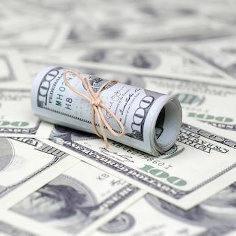 Amerikaanse dollars opgerold en aangespannen met band ligt op veel amerikaanse bankbiljetten
