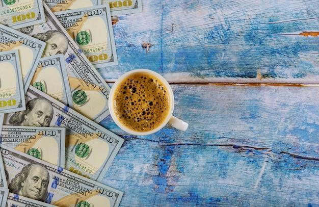 Amerikaanse dollarsbankbiljetten amerikaanse dollars en kop van zwarte koffie op rustieke lijst