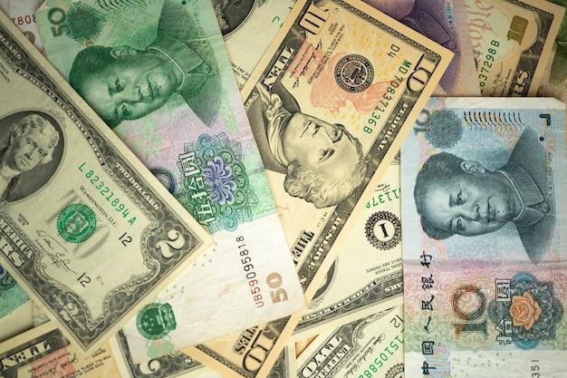 Amerikaanse dollarstapel en chinese yuansbankbiljetten op de lijst
