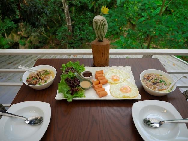 Amerikaanse eieren en worstontbijtset met thaise gehakt varkensvlees zachtgekookte rijst voor paar op houten tafel op terras met uitzicht op de groene natuur