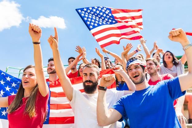 Amerikaanse fans die bij stadion met de vlaggen van de vs toejuichen