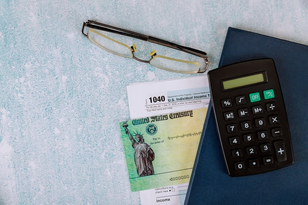 Amerikaanse federale inkomstenbelastingaangifte 1040 van april voor amerikaanse belastingdagtijd met dagelijks notitieblok met rekenmachine