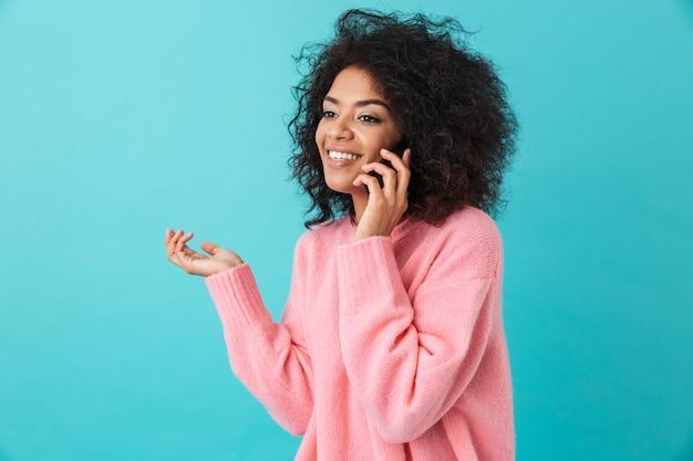 Amerikaanse gelukkige vrouw in roze overhemd dat en op zwarte mobiele telefoon glimlacht spreekt, die over blauwe muur wordt geïsoleerd