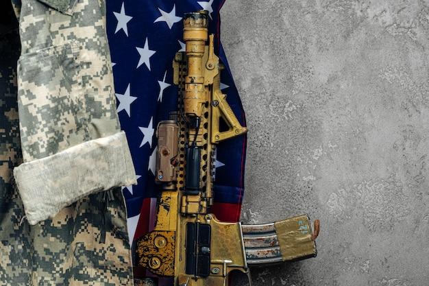 Amerikaanse gevechtsvlag en aanvalsgeweer in de buurt van de muur. detailopname.