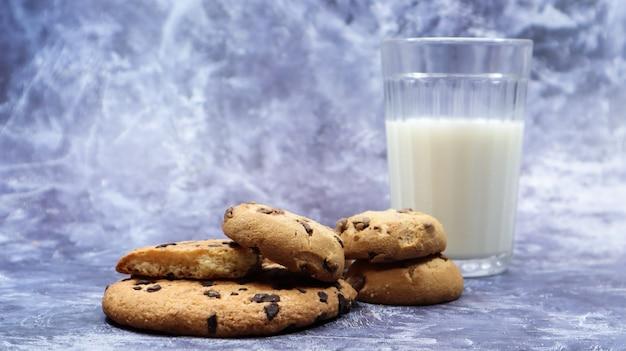 Amerikaanse glutenvrije chocoladeschilferkoekjes met glas glas plantaardige melk op grijze achtergrond. chocolade koekjes. zoet gebak, dessert. culinaire achtergrond. ruimte kopiëren