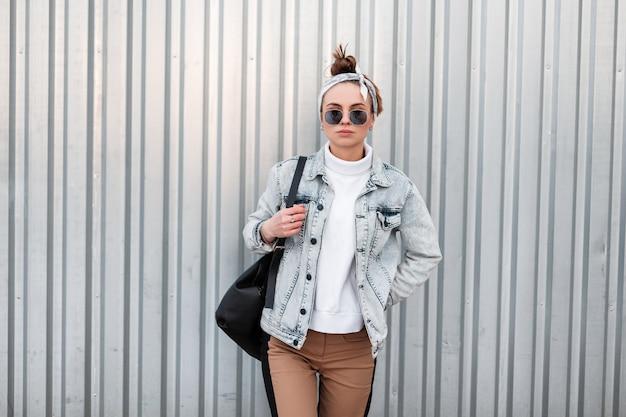 Amerikaanse hipster jonge vrouw met een stijlvol kapsel in zomer denim jassen in trendy broek in een gebreide witte trui in zonnebril met een bandana in de buurt van een glimmende grijze metalen wand. modern meisje.