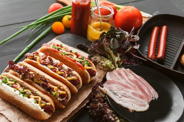 Amerikaanse hotdog met ingrediënten op een donkere houten achtergrond