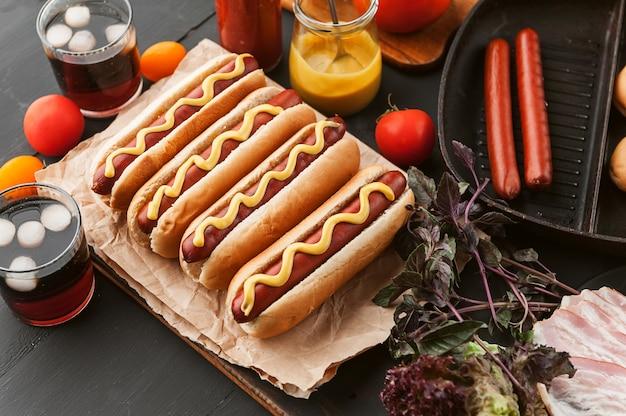 Amerikaanse hotdog met ingrediënten op een donkere houten oppervlak