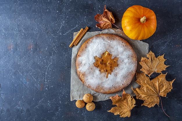 Amerikaanse huisgemaakte pompoen of appeltaart met walnoot en droge herfstbladeren