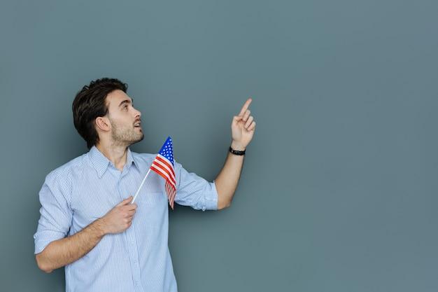 Amerikaanse inwoner. aangename aardige gelukkige man die de amerikaanse vlag vasthoudt en in de richting van zijn hand kijkt terwijl hij een amerikaanse patriot is