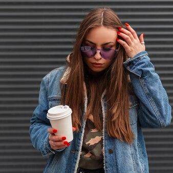 Amerikaanse jonge hipster vrouw in stijlvolle glamoureuze paarse bril in trendy blauw spijkerjasje met koffie rechtzetten haar en neerkijken in de buurt van vintage metalen wand. schattig meisje mannequin buitenshuis.