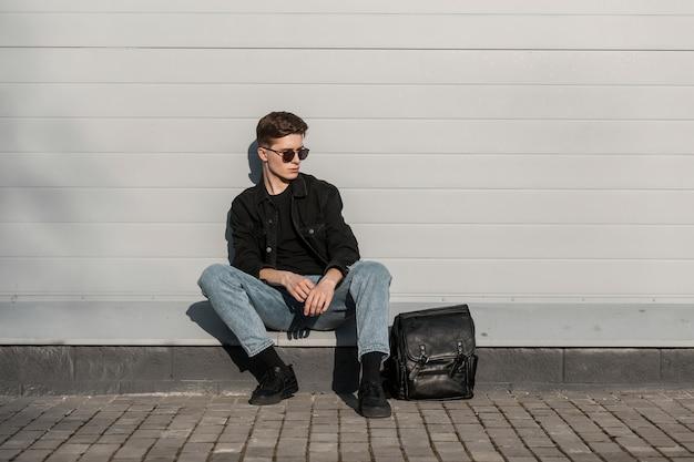 Amerikaanse jonge man in modieuze zonnebril in stijlvolle casual denim kleding in trendy schoenen