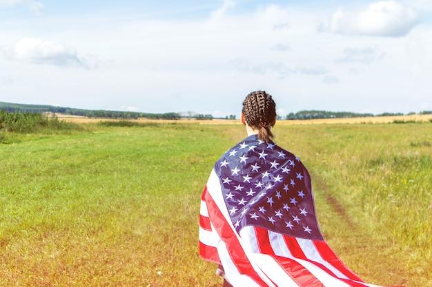 Amerikaanse jonge vrouw met afro-vlechten op een gebied van tarwe verpakt in de vlag van de vs.