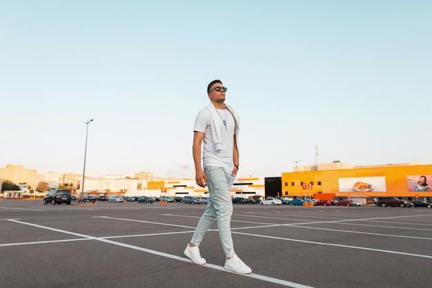 Amerikaanse jongeman hipster in zonnebril in modieuze kleding in trendy witte sneakers reist door de straat.