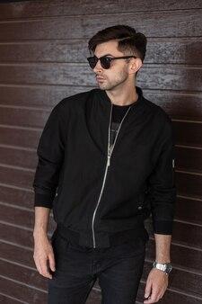 Amerikaanse jongeman in modieuze zwarte kleding in stijlvolle zonnebril met trendy kapsel staat in de buurt van een vintage bruin houten muur in de stad. knappe stedelijke kerel. straatmode. herenkleding.