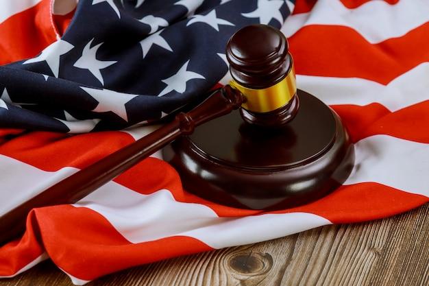 Amerikaanse juridische kantoor met amerikaanse advocaten in de hamer van de rechter op amerikaanse vlag houten tafel