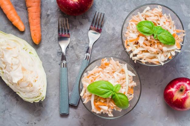 Amerikaanse kant-en-klare cole slaw salade van kool, selderij, wortelen en appels met basilicumbladeren in glazen kommen in de ingrediënten voor het koken op de tafel. het concept van gezonde en goede voeding.