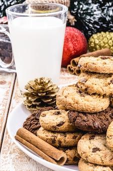 Amerikaanse kersttraditie, koekje voor de kerstman op een bord, met een glas onscherpe melk op de achtergrond