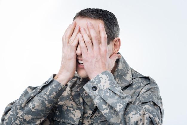 Amerikaanse leger. aardige knappe militaire man die tegen de achtergrond staat en zijn gezicht bedekt terwijl hij over het probleem nadenkt