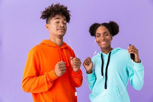 Amerikaanse man en vrouw in kleurrijke kleding dansen terwijl u luistert naar muziek samen met koptelefoon, geïsoleerd op violet muur