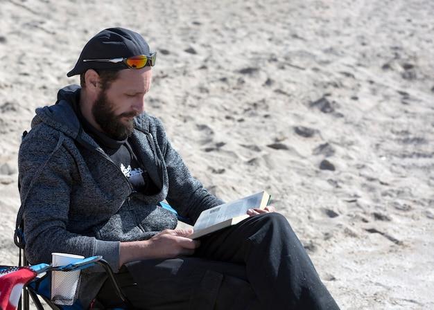 Amerikaanse man ontspannen op een boek lezen op het strand tijdens zonsondergang. russische man leesboek in ligstoel met uitzicht op zee. knappe blanke bebaarde man met zonnebril, pet en capuchonjasje