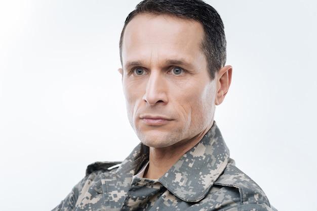 Amerikaanse marine. portret van een slimme aardige doordachte militair die zich tegen terwijl achtergrond bevindt terwijl hij aan het land denkt
