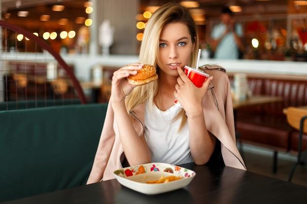 Amerikaanse mooie jonge modelvrouw die snel voedsel in een restaurant eet
